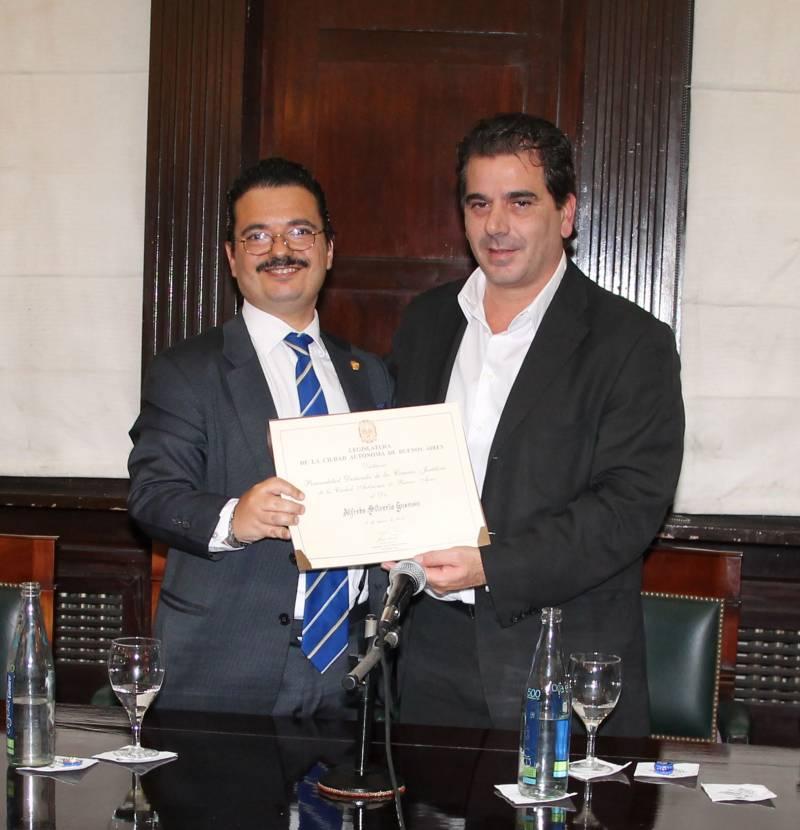 El profesor Alfredo Silverio Gusman recibe la mención de manos del Vicepresidente Primero de la Legislatura porteña, Cristian Ritondo.