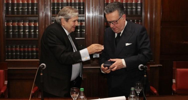 El vicedecano Alberto Bueres entrega el diploma y la medalla que acreditan a Miguel Herrero y Rodríguez de Miñón como doctor honoris causa de la UBA.
